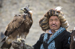 Mongolian nomad eagle hunter with his eagle. Bayan Ulgii, Mongolia, October 2nd, 2015: Old eagle hunter with his Altai Golden Eagle Stock Images