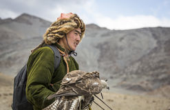 Mongolian nomad eagle hunter with his eagle. Bayan Ulgii, Mongolia, October 2nd, 2015: Old eagle hunter with his Altai Golden Eagle Royalty Free Stock Image