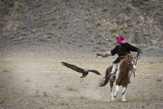 Mongolian nomad eagle hunter with his eagle following him on his horse Royalty Free Stock Photos