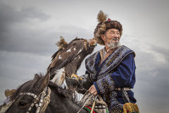 Mongolian nomad eagle hunter on his horse. Bayan Ulgii, Mongolia, October 2nd, 2015: Old eagle hunter with his Altai Golden Eagle on his horse stock images