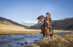 Mongolian nomad eagle hunter on his horse. Bayan Ulgii, Mongolia, October 2nd, 2015: Old eagle hunter with his Altai Golden Eagle on his horse Royalty Free Stock Photos