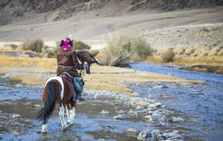 Mongolian nomad eagle hunter on his horse Royalty Free Stock Photography