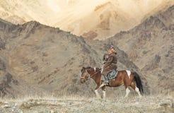 Mongolian nomad eagle hunter on his hotse Stock Photo