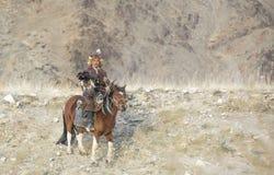 Mongolian nomad eagle hunter on his hotse Stock Photos