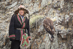 Mongolian nomad eagle hunter in traditional outfit. Bayan Ulgii, Mongolia, October 2nd, 2015:  Kazakh eagle hunter in traditional outfit with his Altai Golden Stock Image