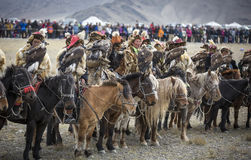 Mongolian nomad eagle hunters lined up on their horses royalty free stock images