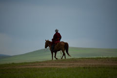 Mongolian Nomad on horse sky. A lone Mongolian nomad rides across the green hills of the green steppe with blue sky in the background Royalty Free Stock Photo