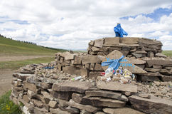 Mongolian Sacred Ovoo. A sacred mound of rocks called an ovoo with blue fabric and religious icons around the edges Stock Photography