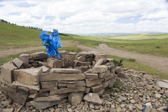 Mongolian Sacred Ovoo. A sacred mound of rocks called an ovoo with blue fabric and religious icons around the edges Stock Photos