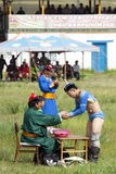 Mongolian Wrestler. A Mongolian wrestler accepts cheese curd from a judge after a wrestling match Royalty Free Stock Images