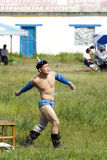 Mongolian Wrestler. A Mongolian wrestler throwing cheese curds into the air after a match as per ancient tradition Stock Photos