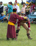 Mongolian Wrestler and Trainer. A Mongolian wrestler prepares for a match with his trainer Royalty Free Stock Images