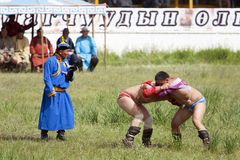 Mongolian Wrestling Match. Mongolian wrestlers in a match as their trainers look on Stock Photo