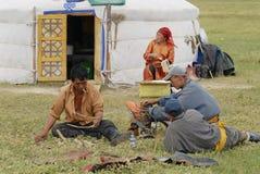 Mongolians fix traditional horse saddle, circa Harhorin, Mongolia. Royalty Free Stock Image
