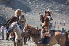 Mongolische kasachische traditionelle Kleidung Eagle Hunters, einen Steinadler auf seinem Arm halten Stockfotos