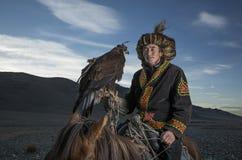 Mongolischer Adlerjäger mit seinem Adler und Pferd Stockfoto