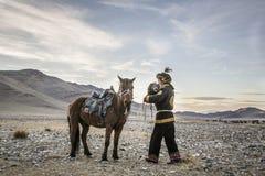 Mongolischer Adlerjäger mit seinem Adler und Pferd Stockbild