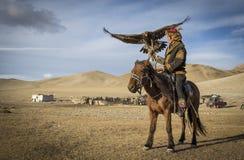 Mongolischer Adlerjäger mit seinem Adler und Pferd Stockfotos