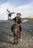 Mongolischer Adlerjäger mit seinem Adler und Pferd Lizenzfreies Stockfoto