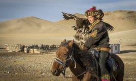 Mongolischer Adlerjäger mit seinem Adler und Pferd Lizenzfreie Stockbilder
