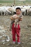 Mongolischer Junge, der Baby-Ziege hält Lizenzfreies Stockfoto