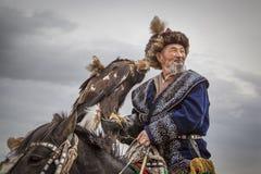 Mongolischer Nomadeadlerjäger auf seinem Pferd Stockbilder
