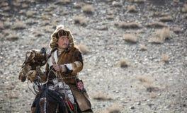 Mongolischer Nomadeadlerjäger auf seinem Pferd Lizenzfreie Stockbilder