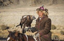 Mongolischer Nomadeadlerjäger auf seinem Pferd Lizenzfreies Stockfoto