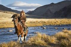 Mongolischer Nomadeadlerjäger auf seinem Pferd Stockbild