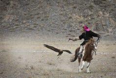 Mongolischer Nomadeadlerjäger mit seinem Adler, der ihm auf seinem Pferd folgt Lizenzfreie Stockfotos