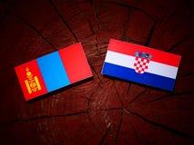 Mongolisk flagga med den kroatiska flaggan på en isolerad trädstubbe Fotografering för Bildbyråer