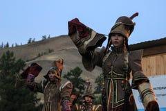 Mongolisk kvinna i medicinman- och häxadräktdanser på etapp i bergen Tyva folkdanser arkivbilder