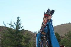 Mongolisk kvinna i medicinman- och häxadräktdanser på etapp i bergen Tyva folkdanser arkivfoton