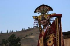 Mongolisk kvinna i medicinman- och häxadräktdanser på etapp i bergen Tyva folkdanser royaltyfri foto
