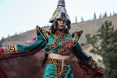 Mongolisk kvinna i medicinman- och häxadräktdanser på etapp i bergen Tyva folkdanser royaltyfri fotografi
