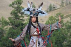 Mongolisk kvinna i medicinman- och häxadräktdanser på etapp i bergen Tyva folkdanser arkivbild
