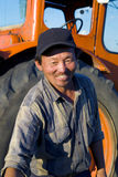 Mongoolse Landbouwer Standing In Front Of His Tractor Reaching Forwa royalty-vrije stock fotografie