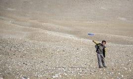 Mongoolse nomadejongen in een landschap van Westelijk Mongolië, het spelen frisbee stock foto's