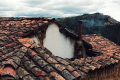 old ceramic tiles on a traditional home with a small chimney smoking stock image