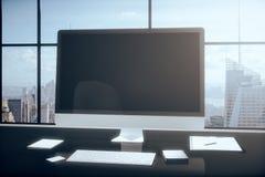 Monitor in bianco del computer con gli accessori dell'ufficio su una tavola in Immagine Stock Libera da Diritti