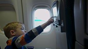 Monitor conmovedor del asiento del niño pequeño en el avión almacen de metraje de vídeo