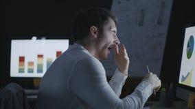 Monitor de computadora delantero de bostezo del analista con exceso de trabajo del negocio en oficina de la noche metrajes