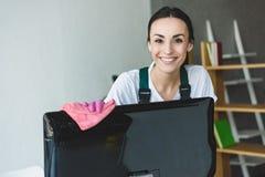 monitor de computadora de limpieza atractivo y sonrisa de la mujer joven foto de archivo libre de regalías