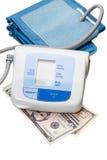 Monitor de la presión arterial de Digitaces y efectivo del dólar Fotos de archivo