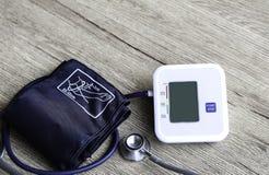 Monitor de la presión arterial de Digitaces en fondo de madera Imagen de archivo libre de regalías