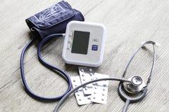 Monitor de la presión arterial de Digitaces en fondo de madera Foto de archivo libre de regalías