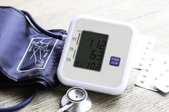 Monitor de la presión arterial de Digitaces en fondo de madera Fotos de archivo libres de regalías