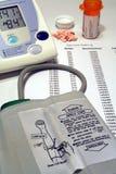 Monitor de la presión arterial, píldoras y registro de la salud Fotos de archivo