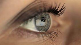 Monitor de vista macro do olho da menina da mulher, surfando filme