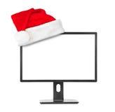 Monitor del computer e cappello rosso di natale di Santa Claus Fotografie Stock